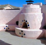 Pink stucco Kiva Fireplace by Mountain Paradise Landscaping, Rio Rancho & Albuquerque, New Mexico