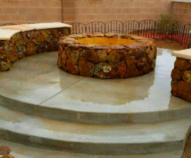Wood burning fire pit made with moss rock and benches by Mountain Paradise Landscaping, Rio Rancho & Albuquerque, New Mexico